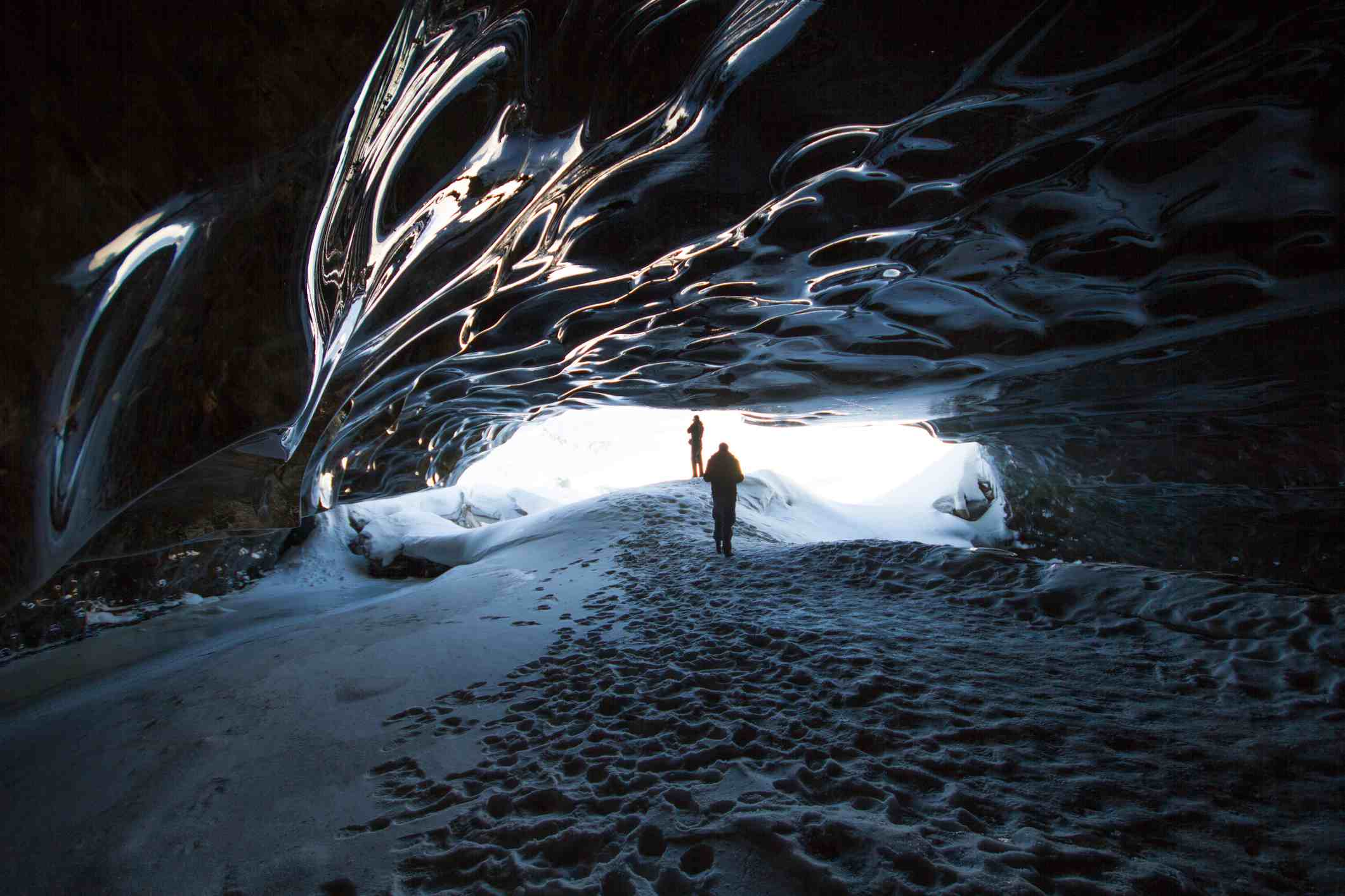 A man is standing right in the mouth of an ice cave in Langjökull, Iceland.