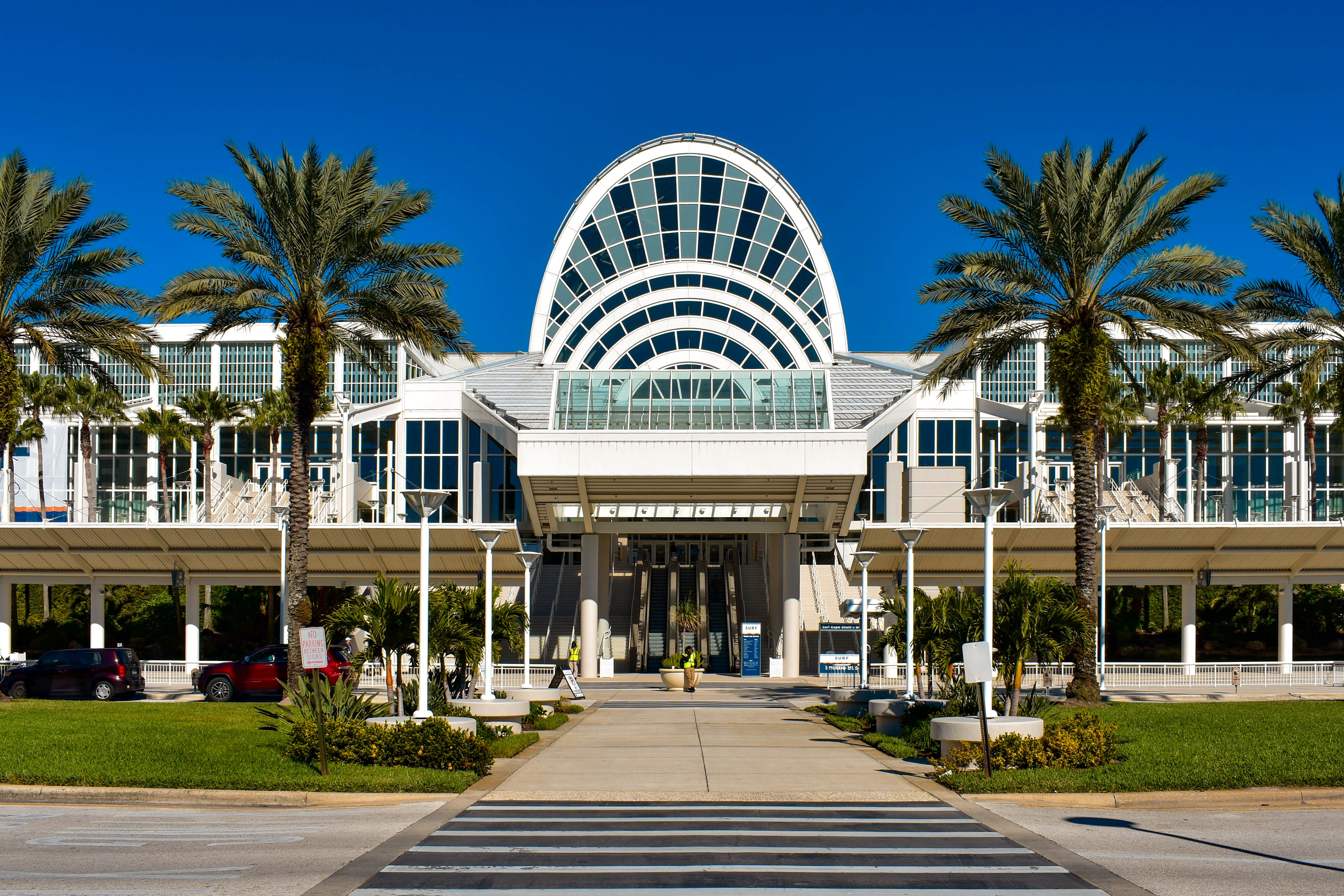 The arches of the main entrance of the Orlando Convention Center beneath a clear blue sky and flanked by palm trees at International Drive area