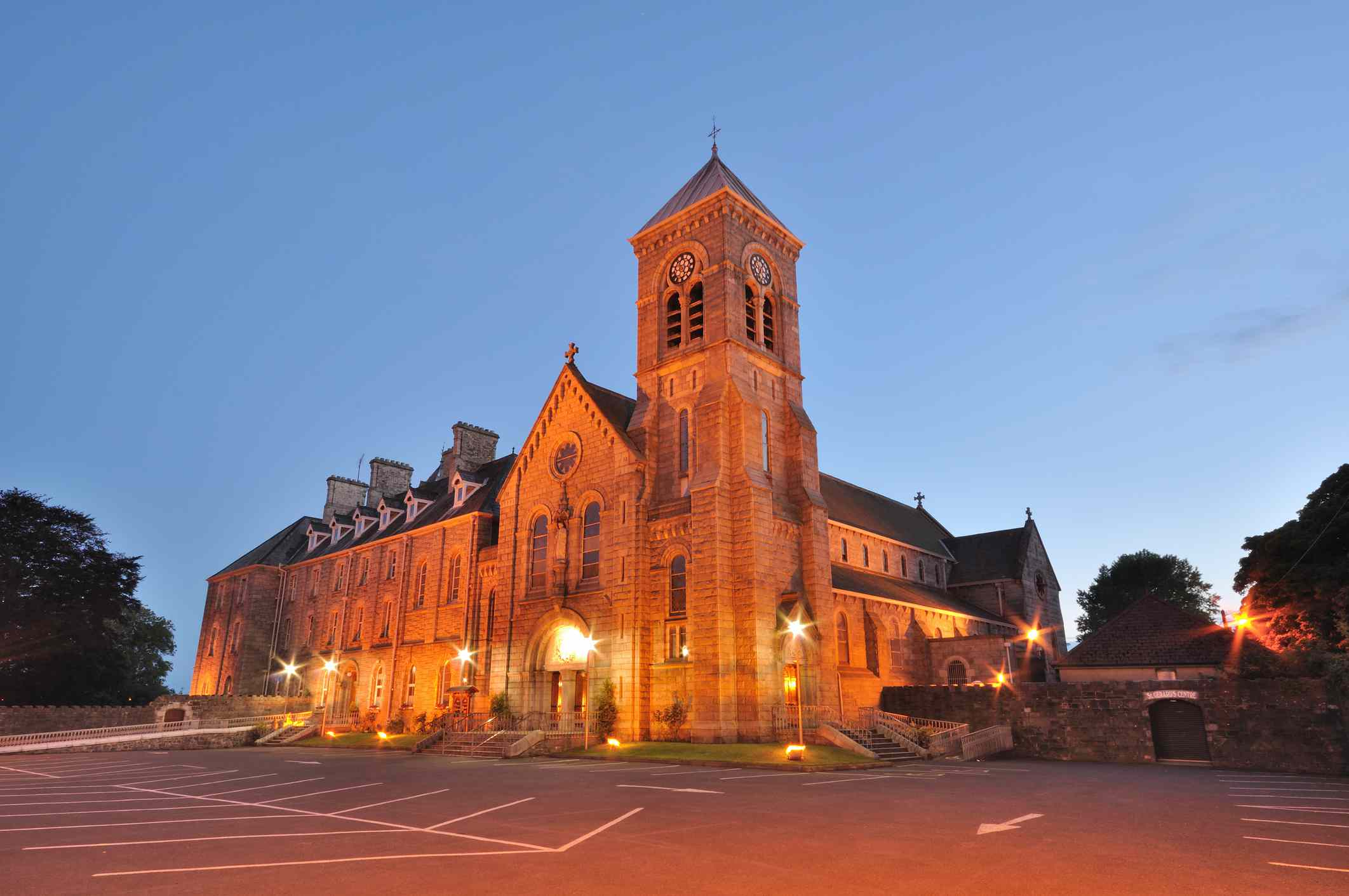 The granite St. Joseph's Redemptorist Church bathed in orange light at twilight