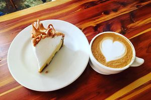 Slice of key lime pie topped with meringue on a plate next to a latte with a heart on it