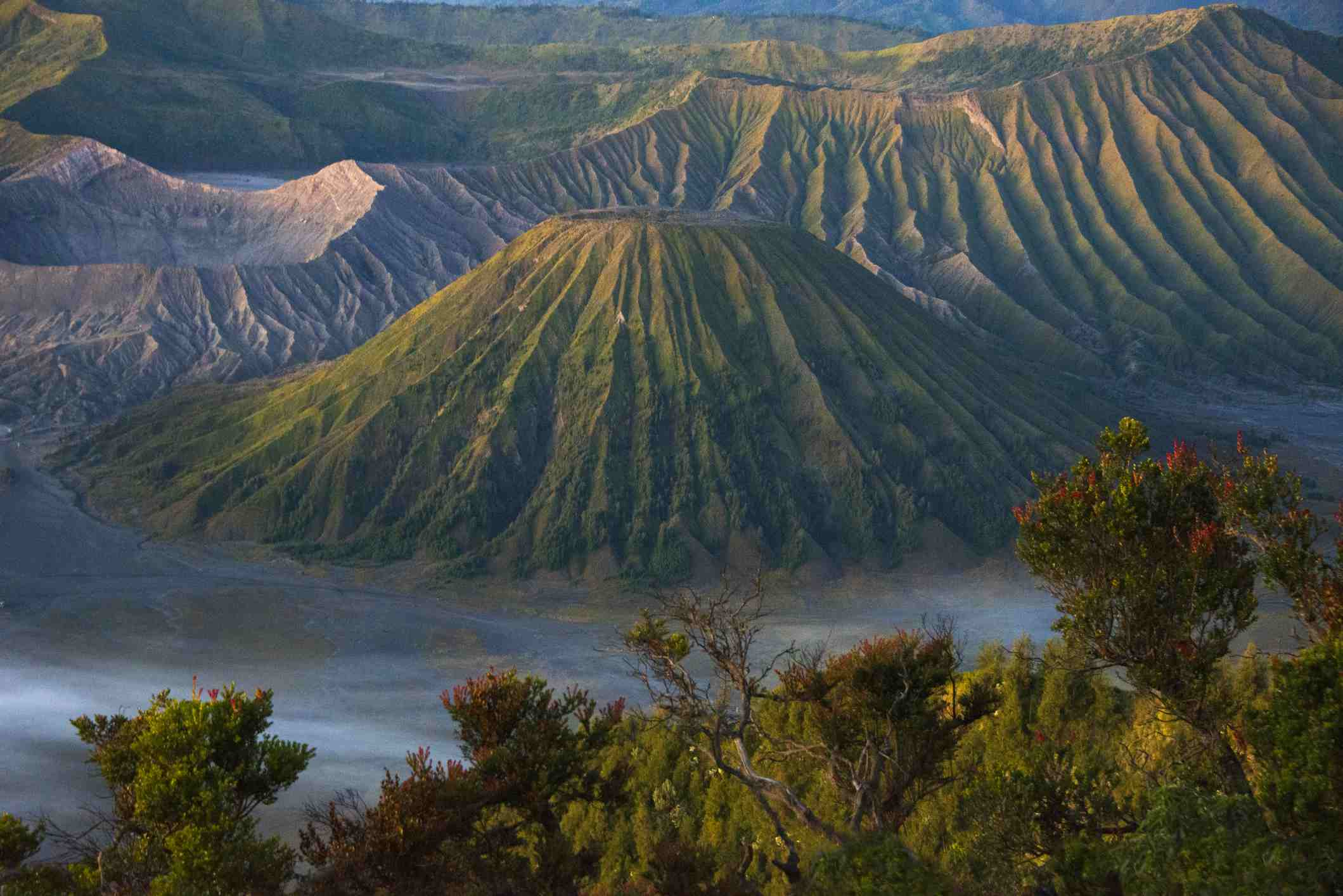 The green, cone-shaped Mount Batok, center, with Mount Bromo to the side