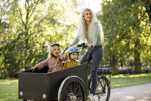 Mother cycling with two children in electric cargo bicycle