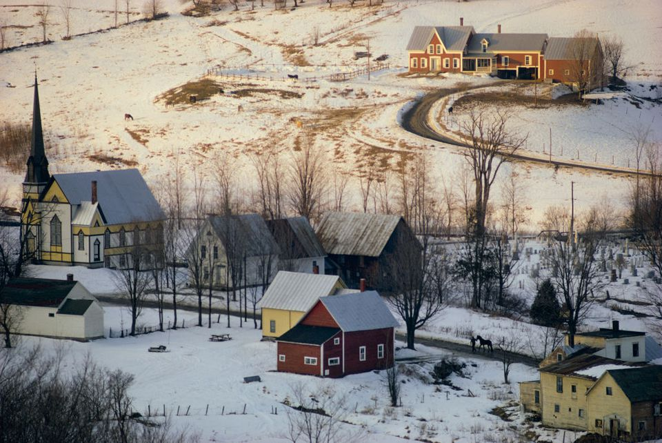 Scenic of rural valley New England village of East Orange, Vermont on a winter day with snow on ground, narrow road, modest buildings and church on January 31, 1974. A person leads a horse down the road, which is cleared of snow. Most of the structures are 19th century