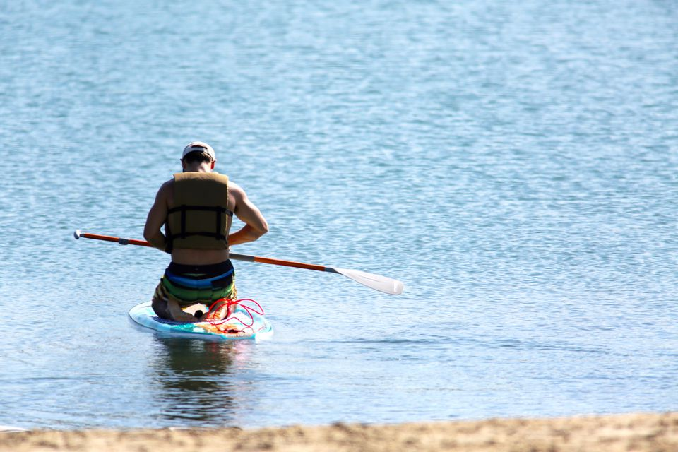man launching stand up paddle board at Long Beach California