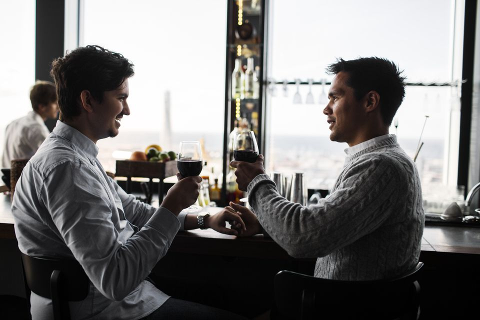 Gay couple toasting with red wine at table in sky bar restaurant