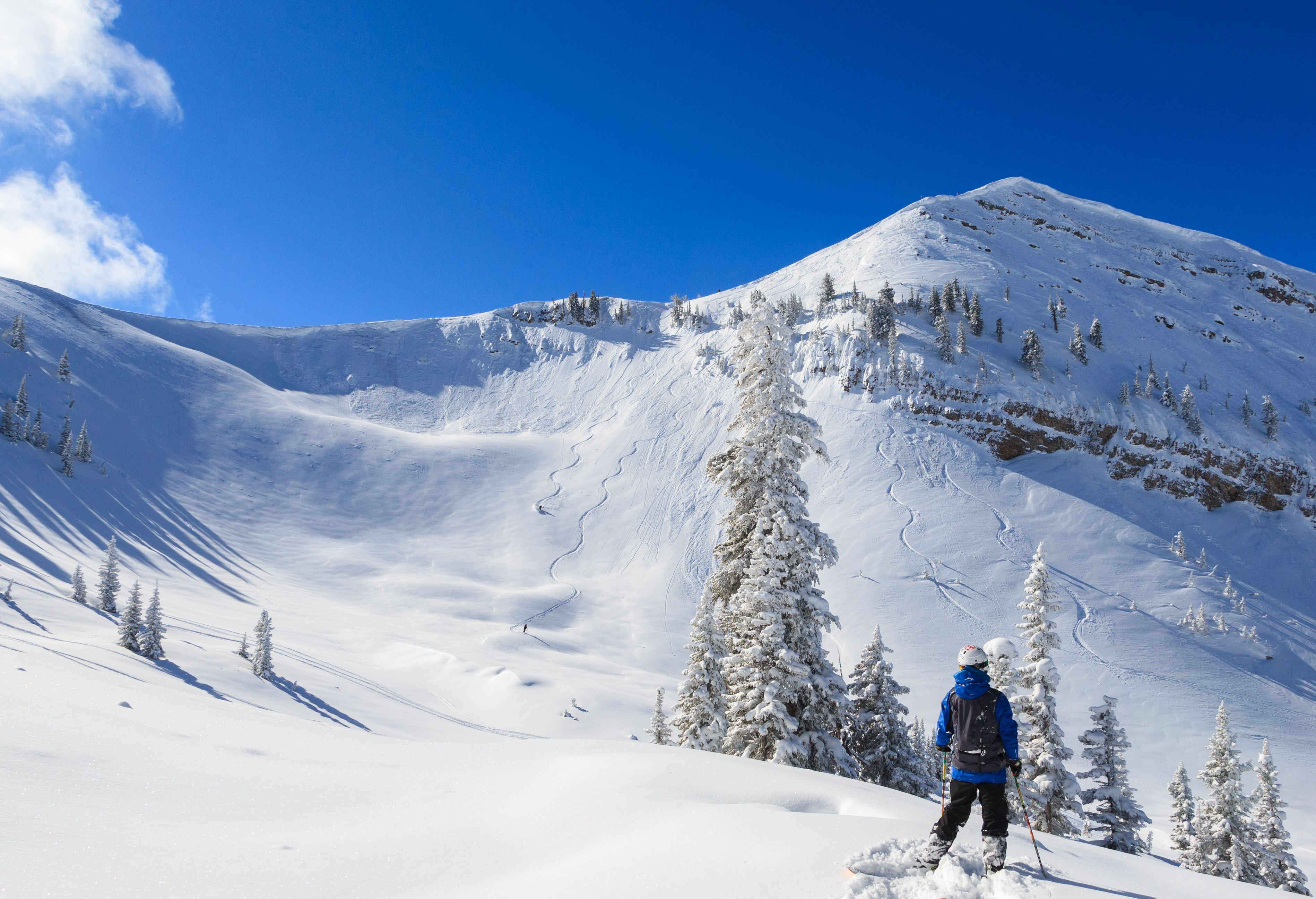 A skier watches two other skiers make tracks down a ski run at Grand Targhee Resort.