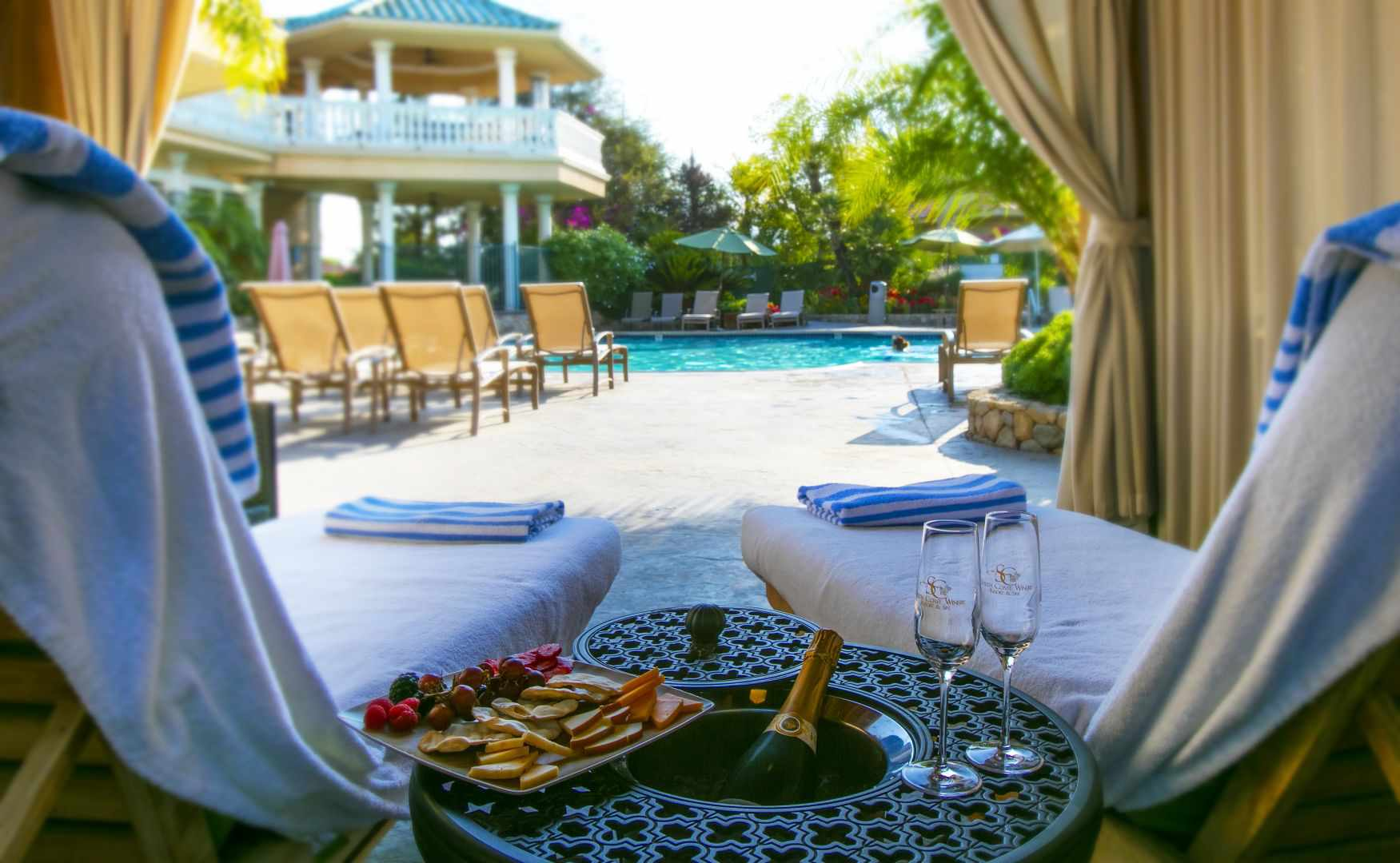 two pool lounge begs in a cabana with a bottle of champagne and charcuterie board in between the beds.