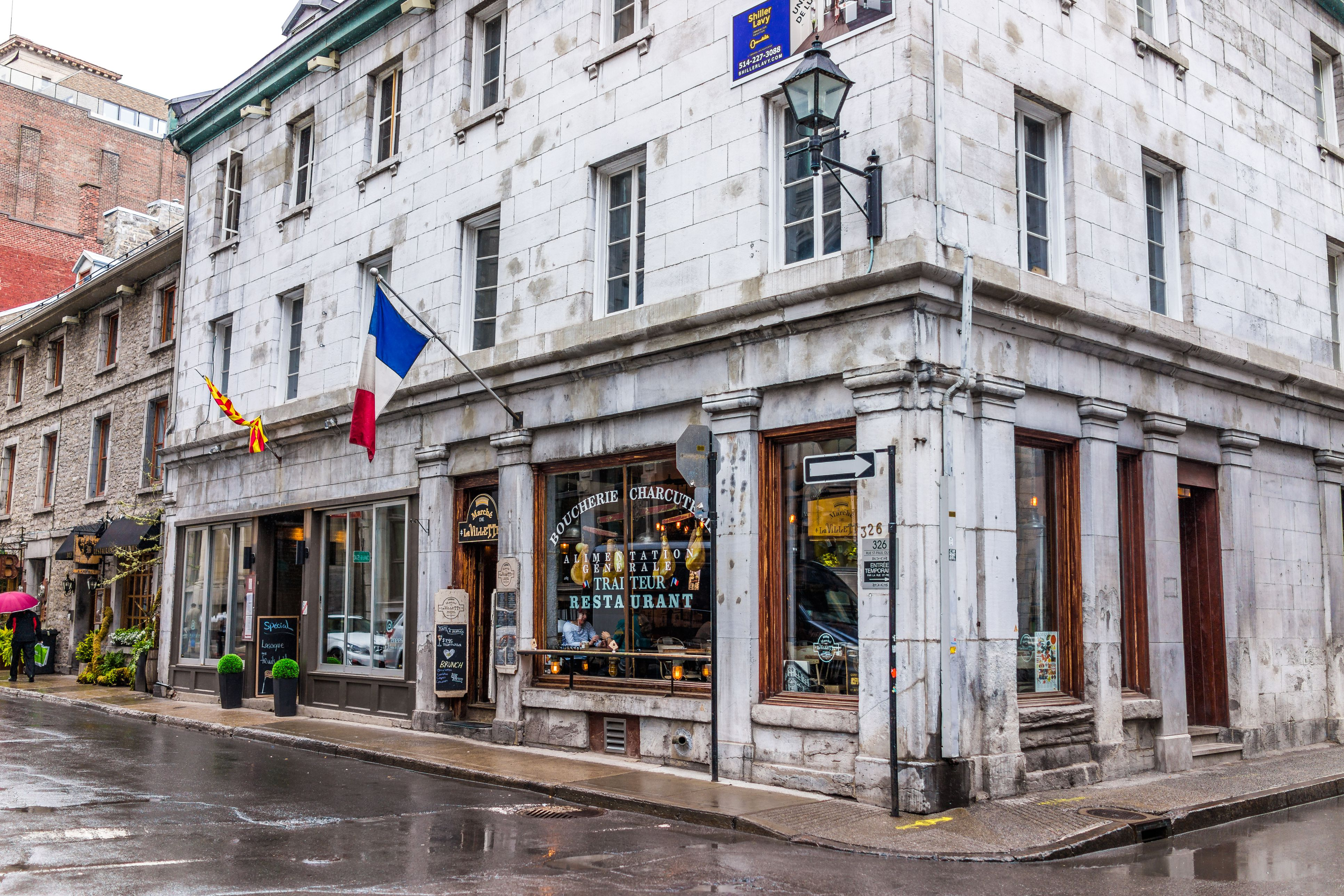 Downtown area of city in Quebec region with restaurants, butcher shop and cafe with French flag during wet rain on cloudy day