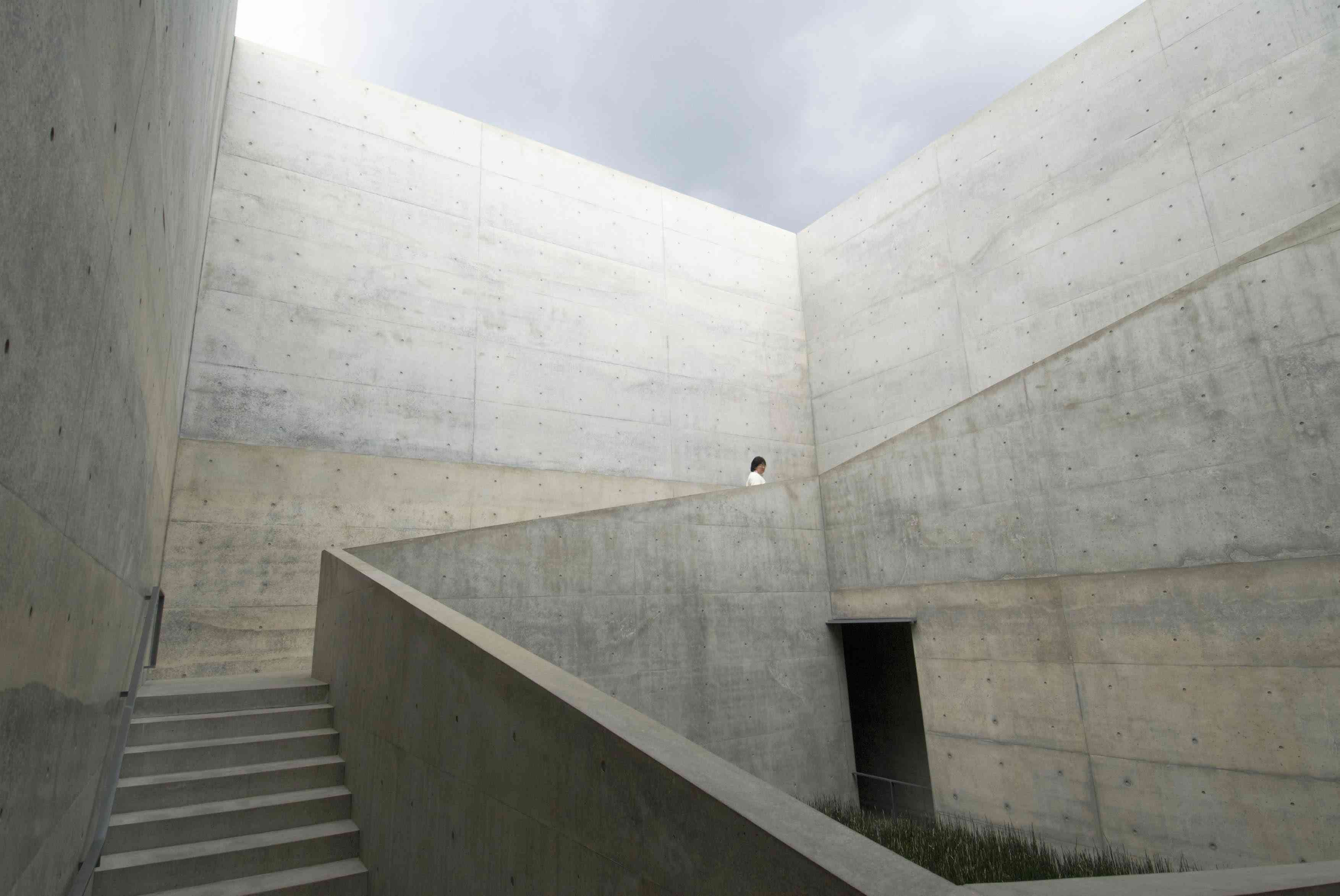 person in a white shirt walking up a staircase is a tall, concrete-colored structure