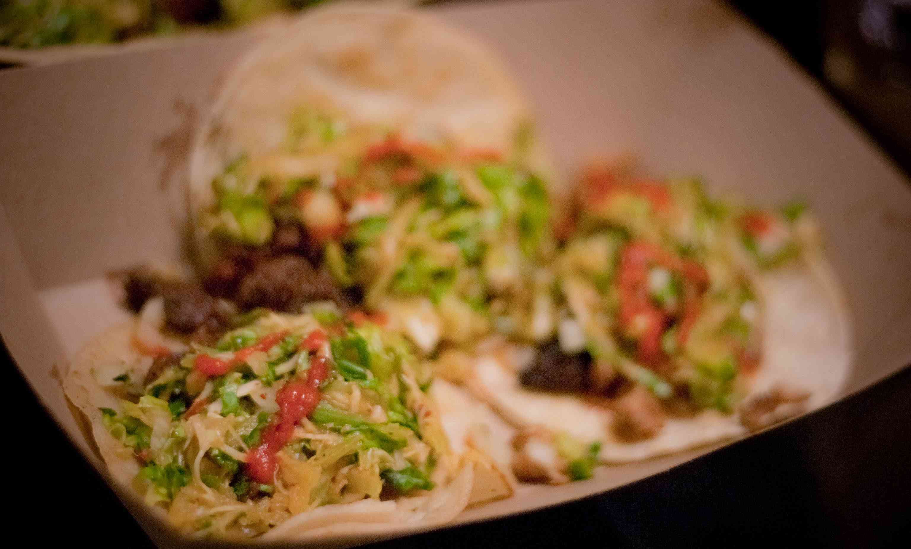Three out of focus tacos from Kogi BBQ in a cardboard tray