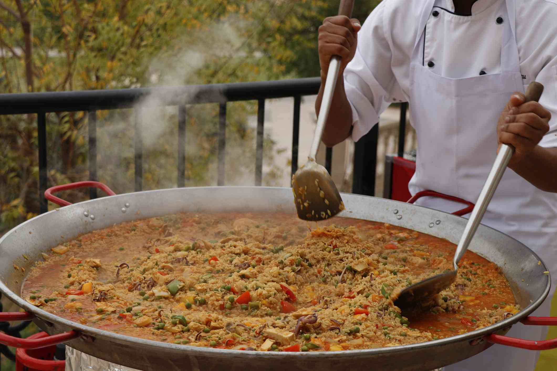 chef cooking Spanish paella in outdoor area