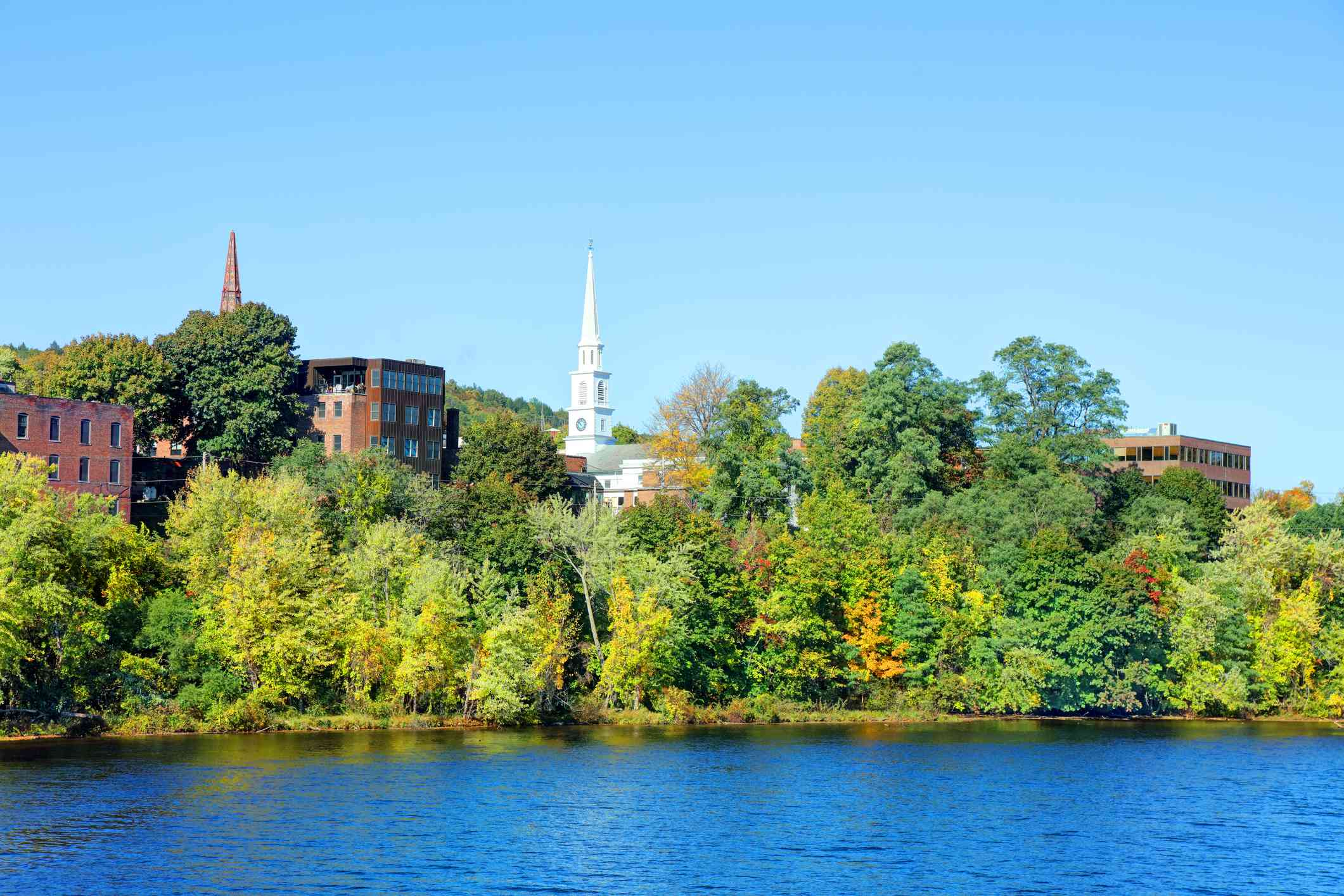 town of Brattleboro, Vermont partially obscured by trees on the banks of the connecticut river