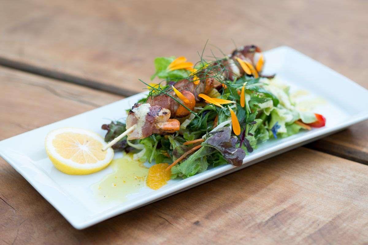 Skewer of meat on salad greens with a slice of lemon