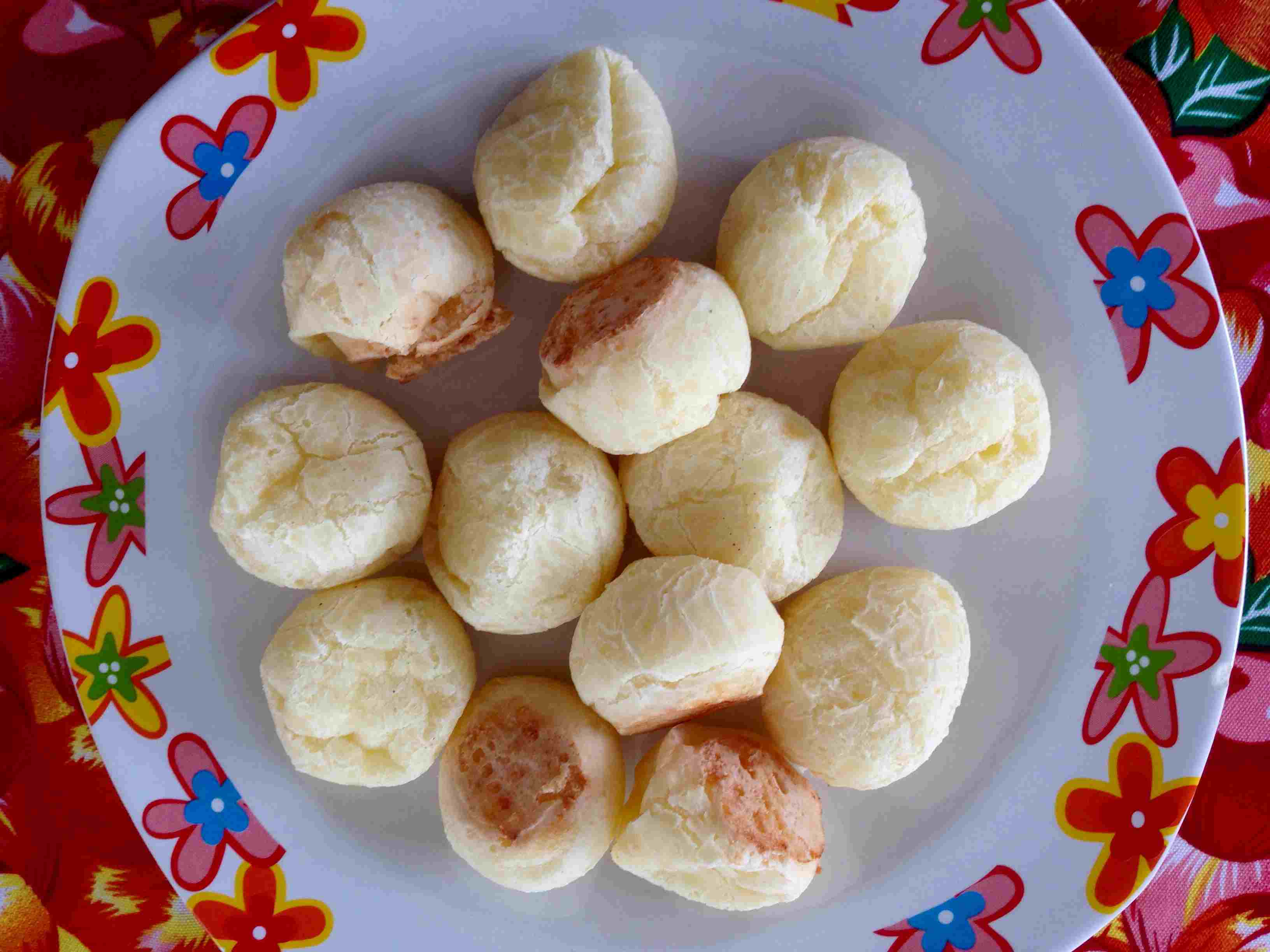 Close up of pao de queijo snack on colorful plate.