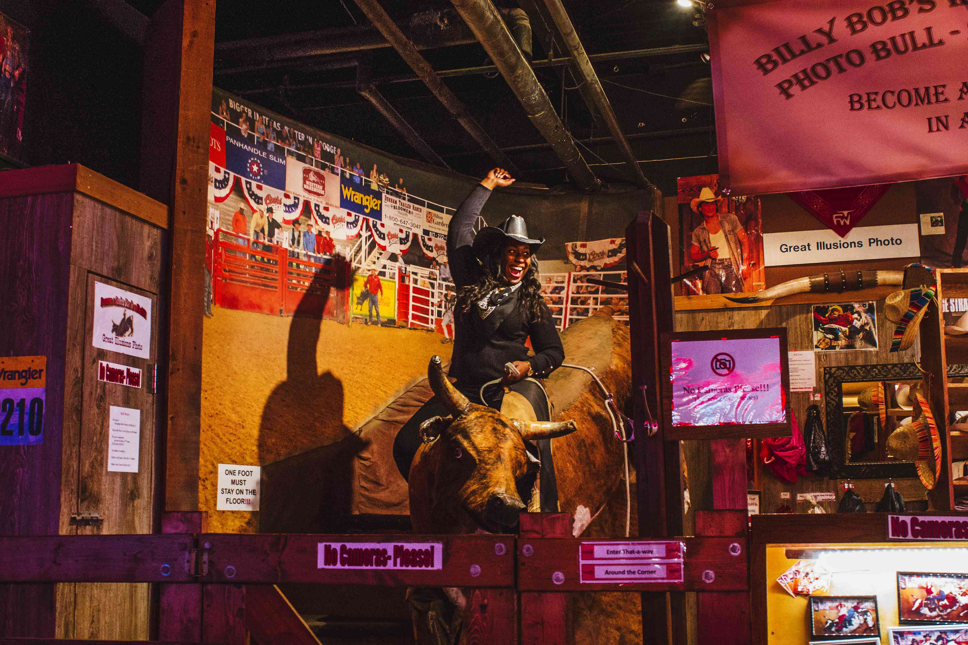 A woman posing on a mechanical bull for a photo at Billy Bob's
