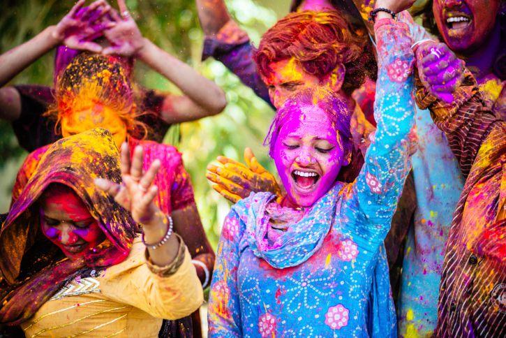 Las mujeres bailan durante el colorido festival de holi