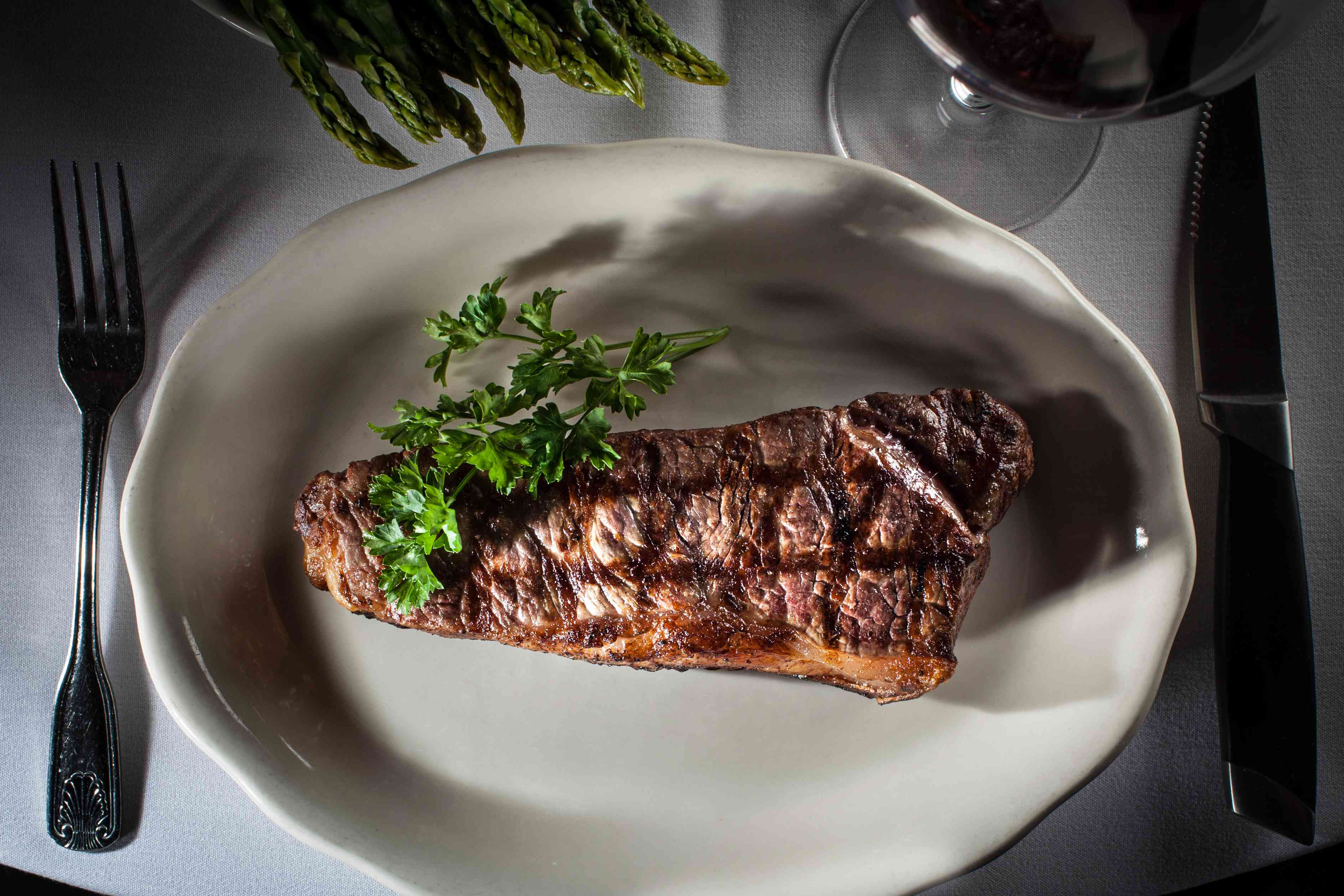 New York strip steak on a plate with a fork and steak knife