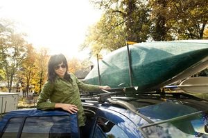 Woman packing kayak on roof of car