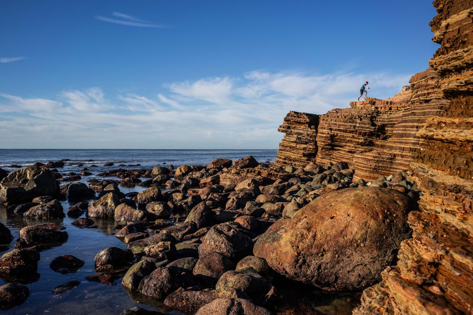 A person climbing up the rocks at the tide pools