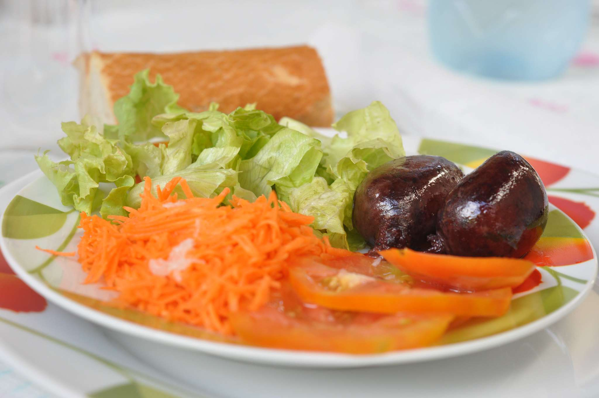 two small blood sausages on a plate with carrots, lettuce, tomatoes and a piece of bread