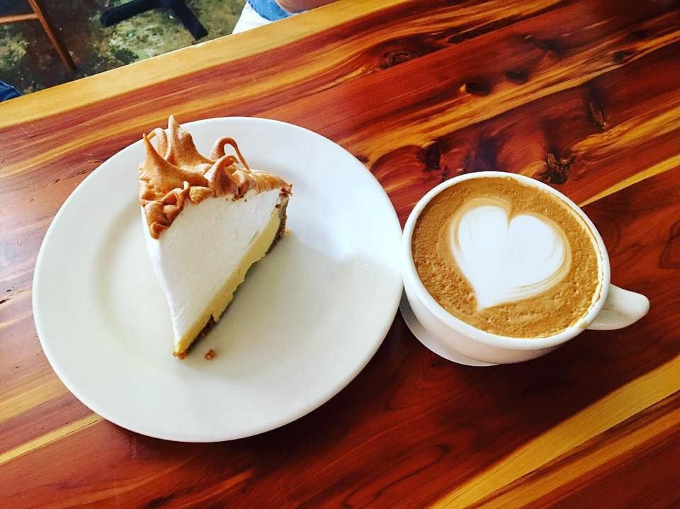Rebanada de tarta de lima cubierta con merengue en un plato junto a un café con leche con un corazón