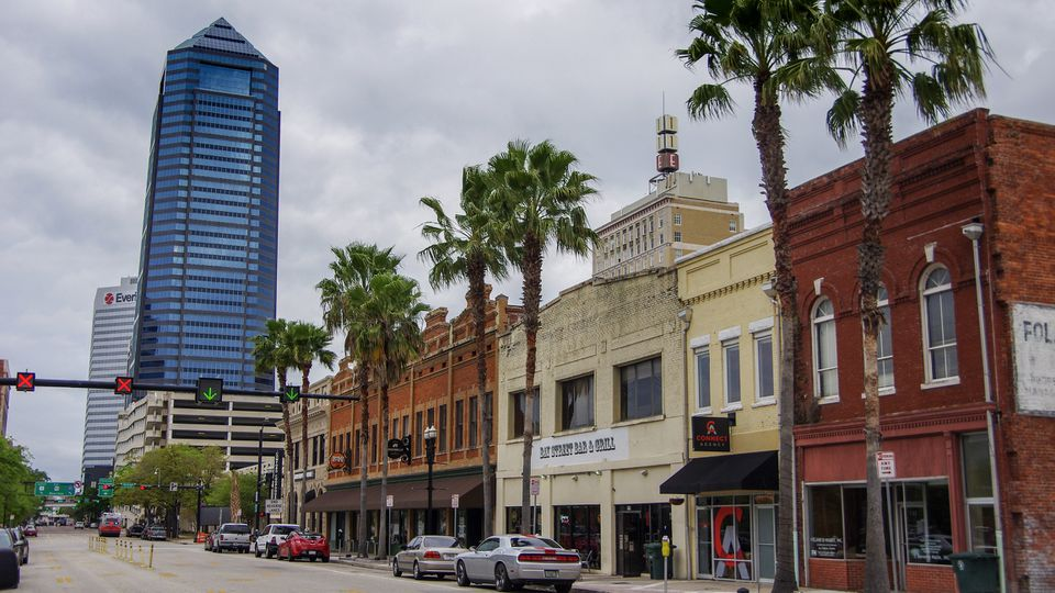Jacksonville Florida cityscape with mix of old and new buildings on palm tree lined street
