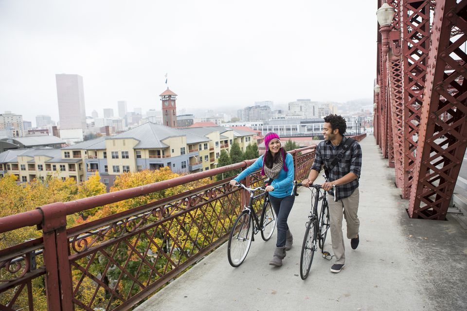 A young couple pushing their bikes across a bridge near downtown Portland, Oregon.