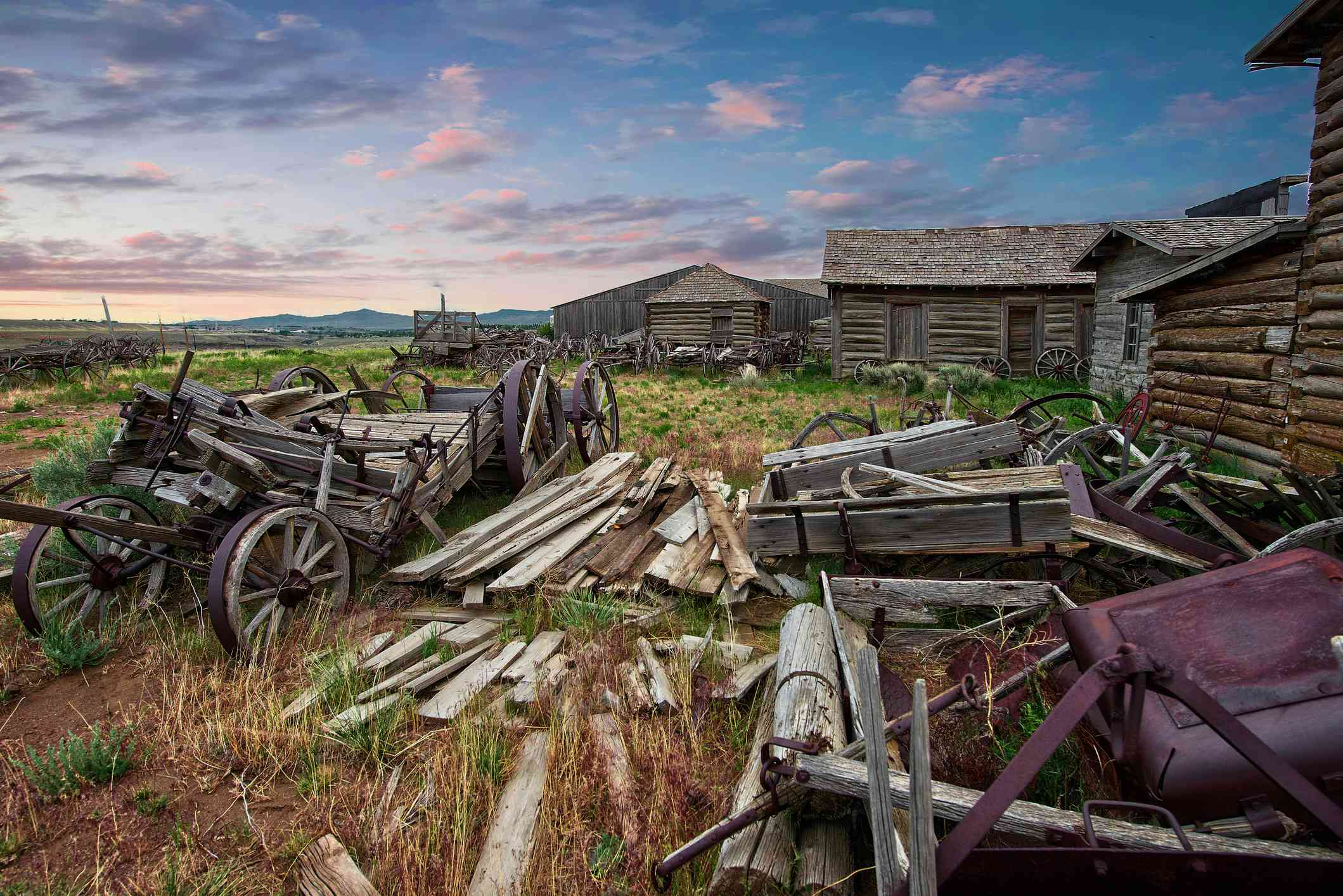 small log houses and broken down wooden wagons in an overgrown field
