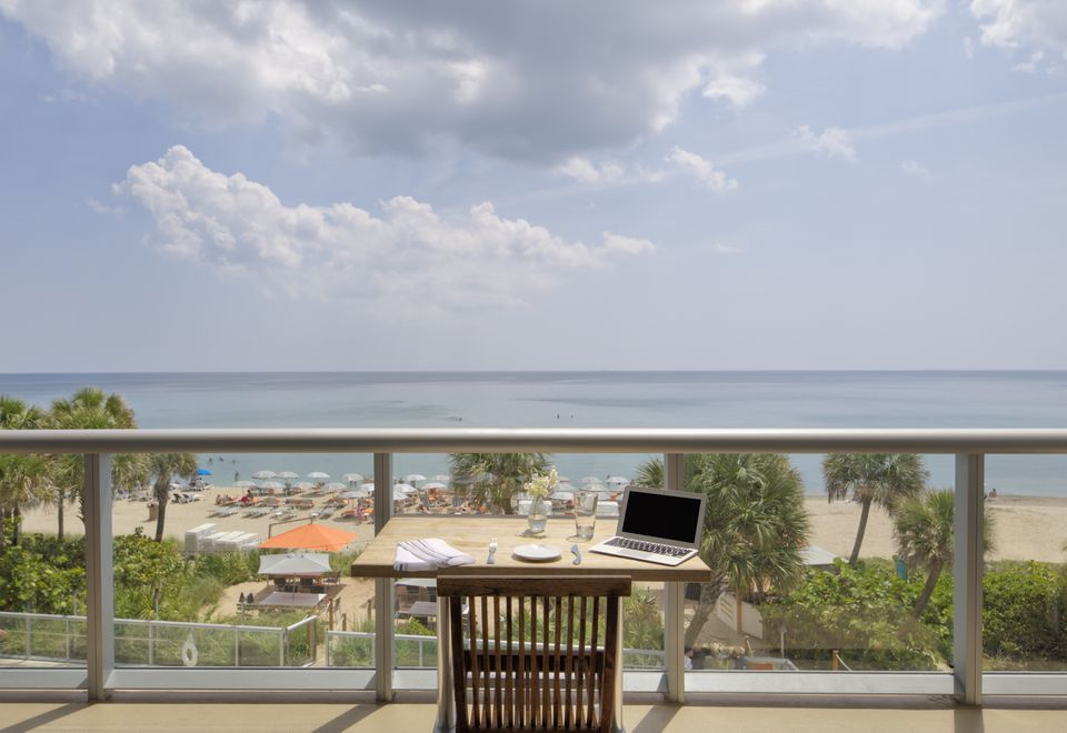 Laptop on restaurant balcony table overlooking beach