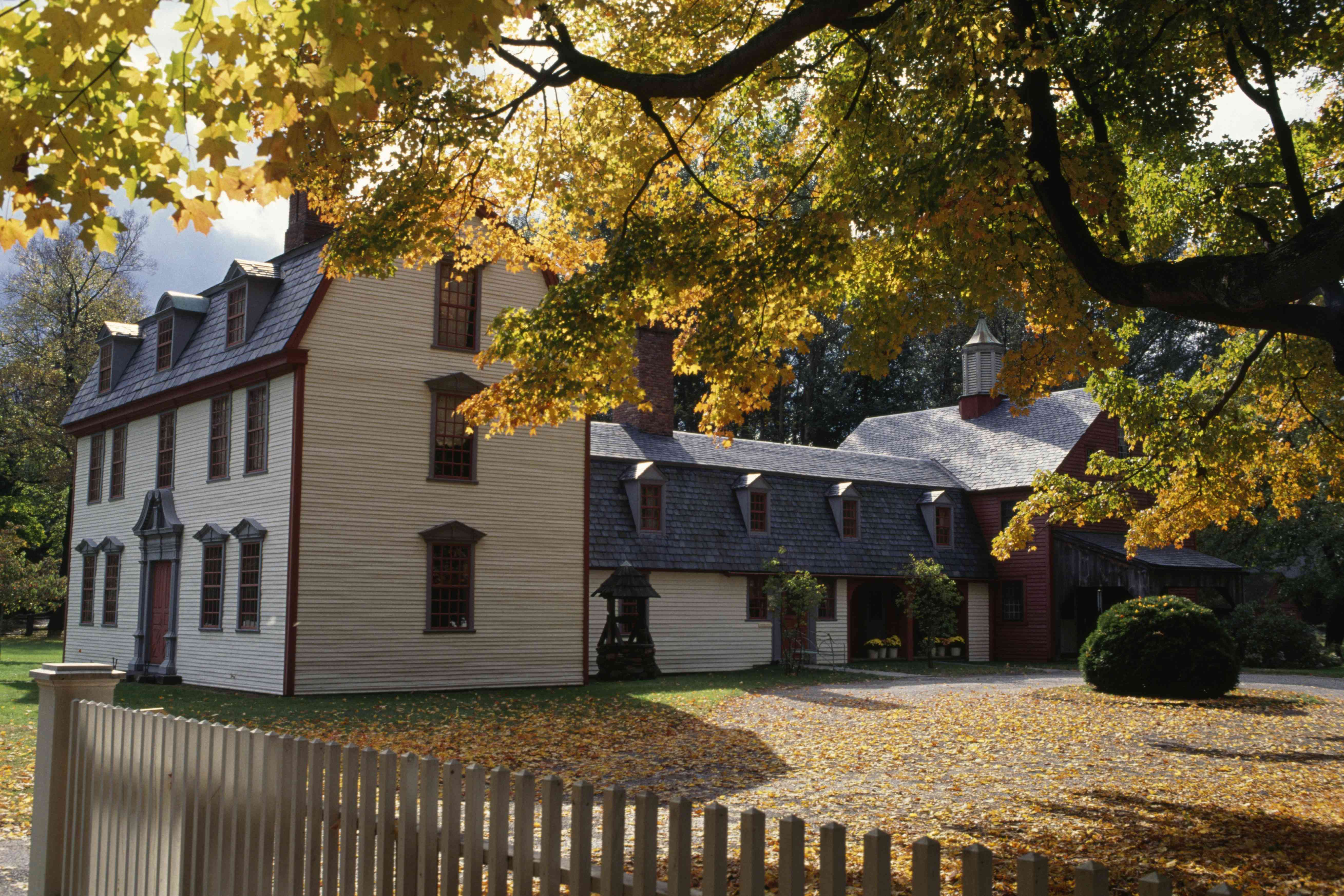 18th-century house with trees in the foreground and leaves on the ground