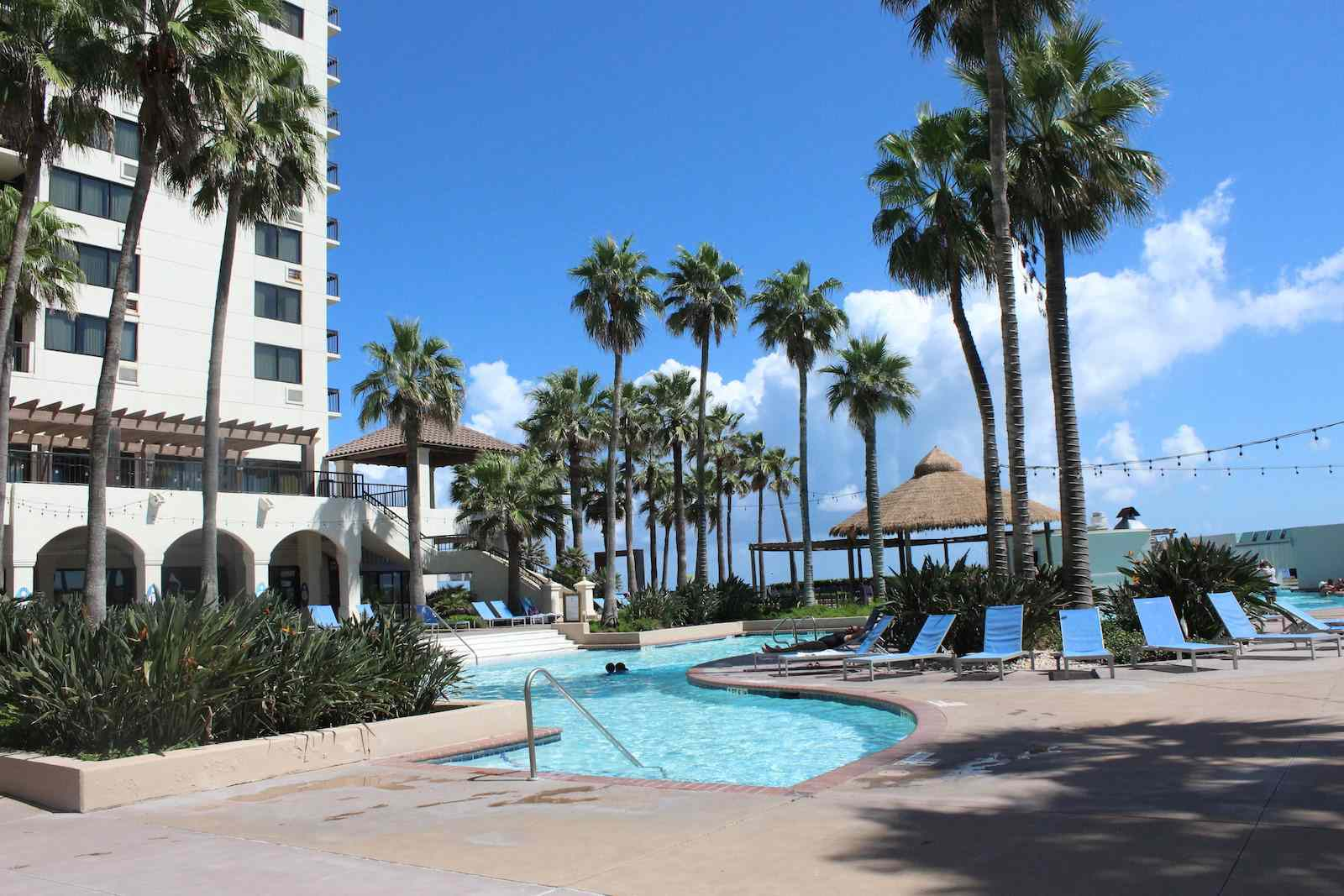 The inviting pool and palm tree-lined courtyard at the Pearl at