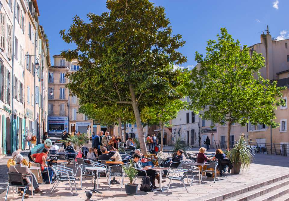 "people sitting on chairs in a square in the ""Les Paniers"" district, Marseille, France"