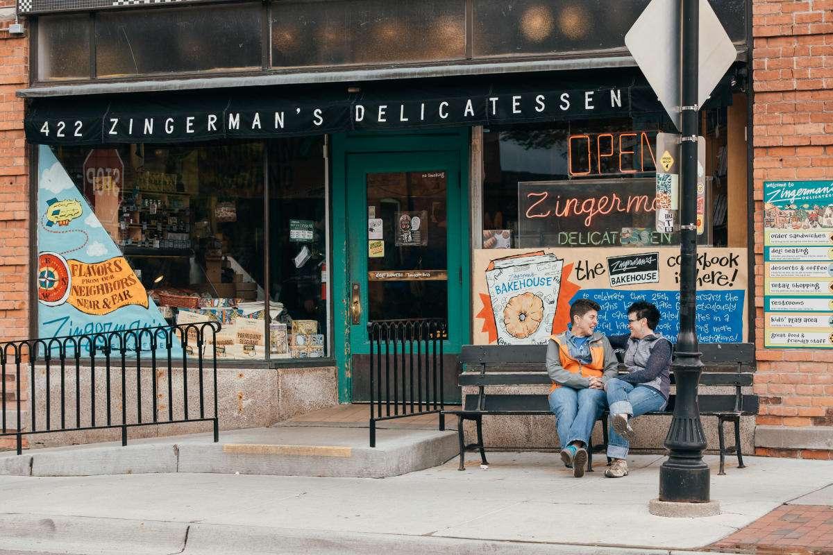 Dos personas sentadas en un banco frente a la tienda de delicatessen de Zingerman en Ann Arbor