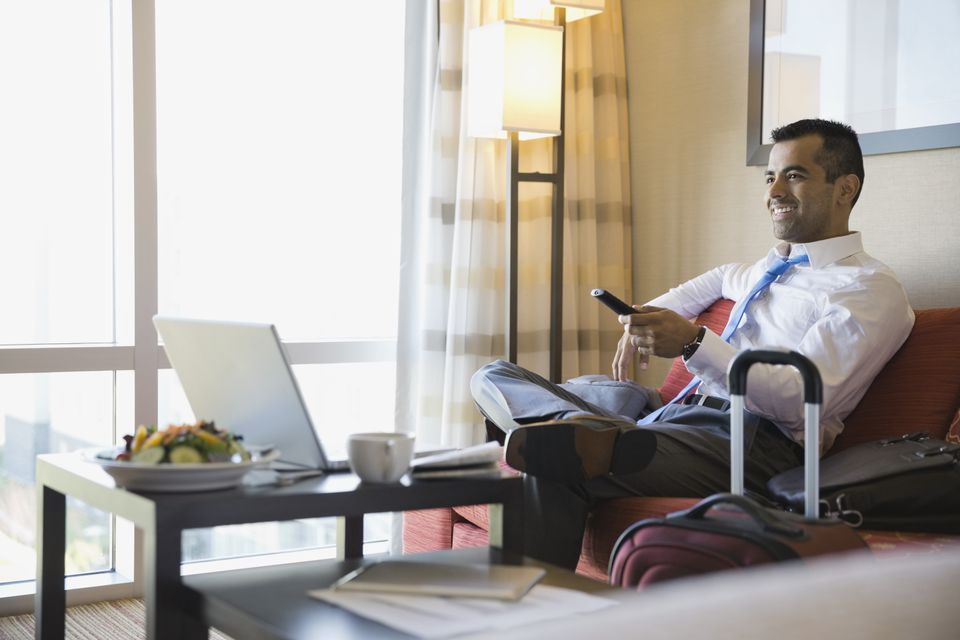Smiling businessman watching TV in hotel room