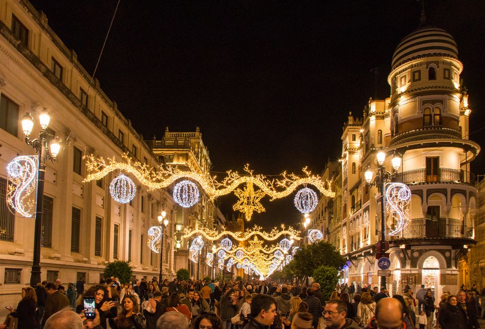 Locals and visitors enjoy Christmas lights in Seville, Spain