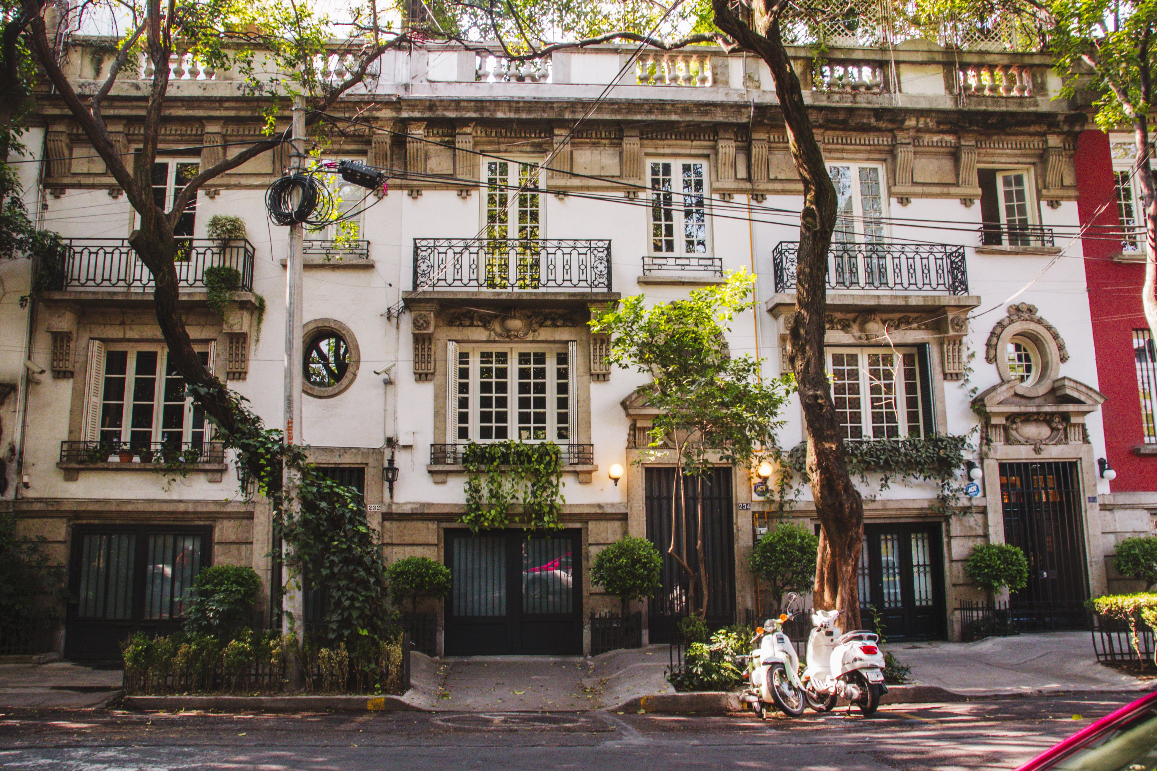 An old colonial building covered in green plants