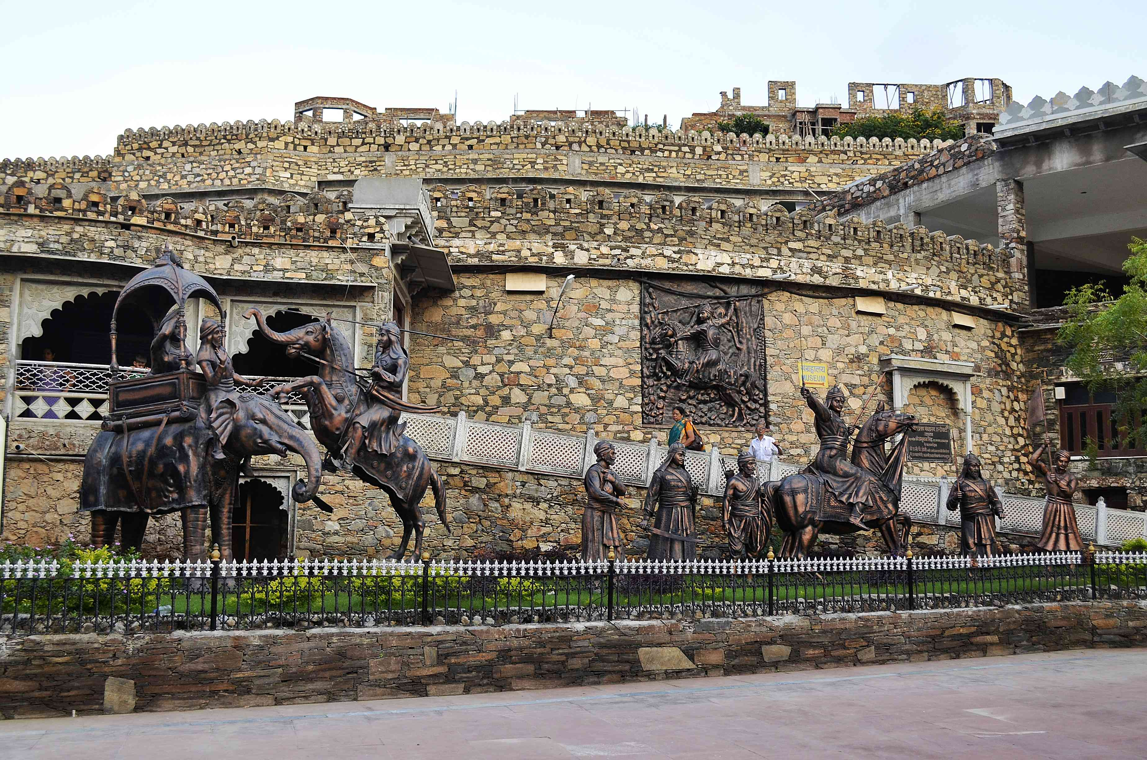 bronze statues of horses and people in front of the stone building (Maharana Pratap Museum)