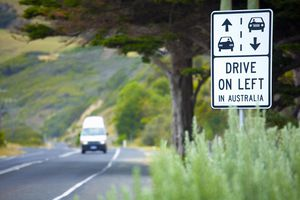 Sign on Great Ocean Road, Victoria, Australia that reads 'Drive on Left in Australia'.A van in the distance approaches in right lane.