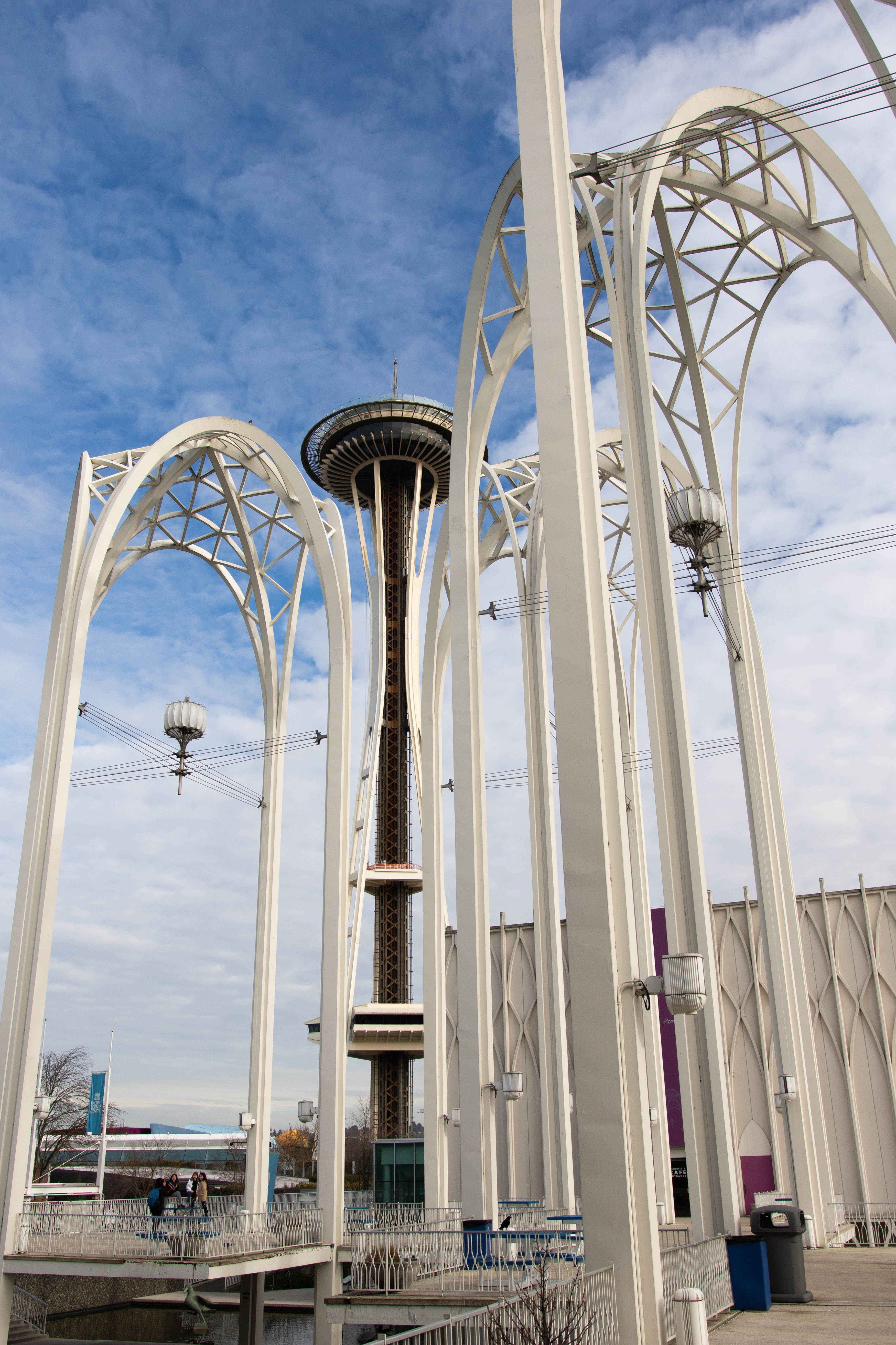 Seattle space needle in view behind tall, white, structures