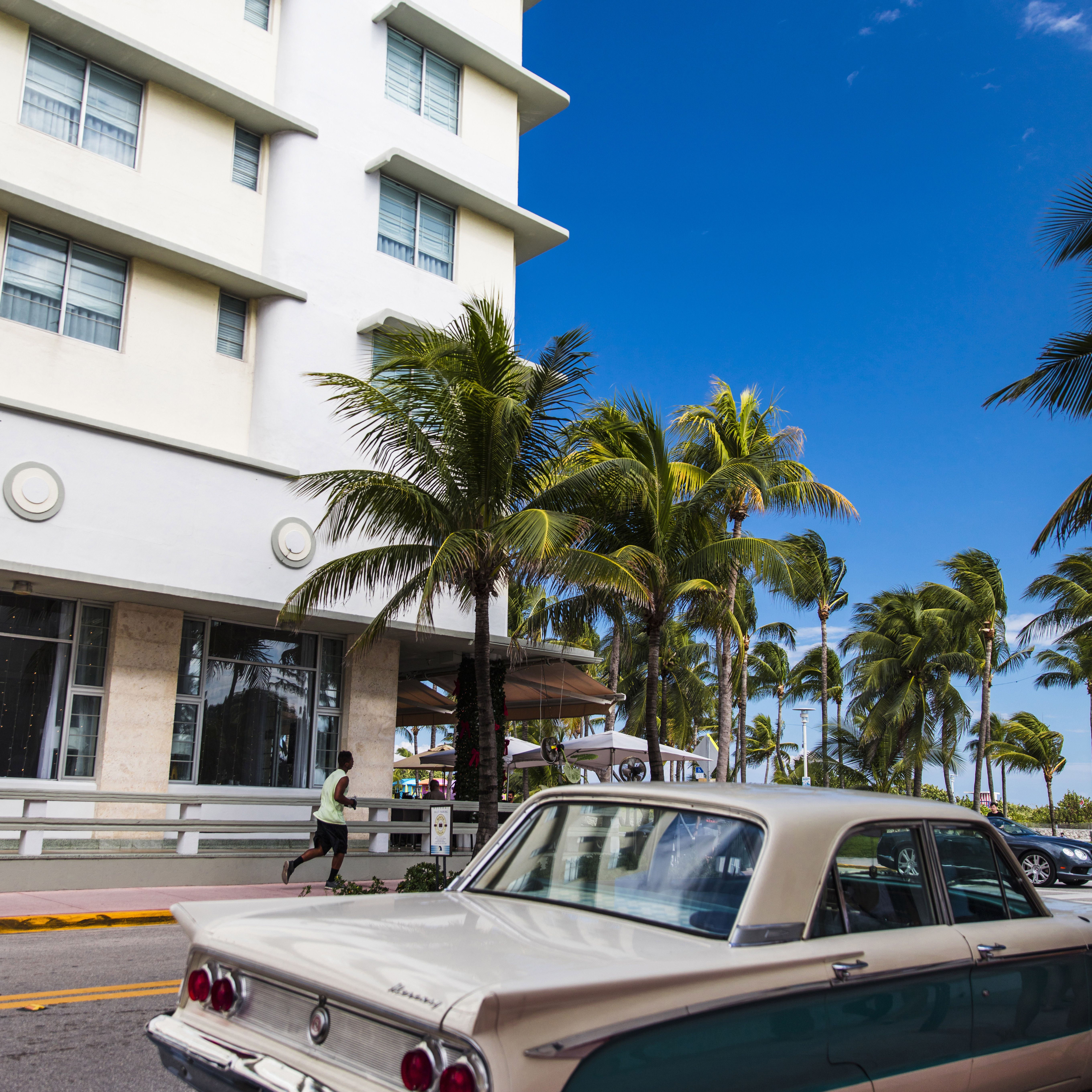 Classic car by palm trees and an art deco hotel in South Beach miami