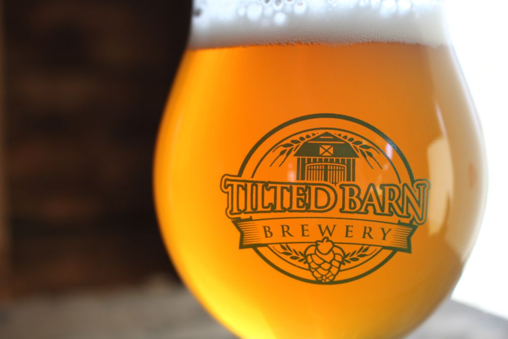 Tilted Barn Brewery beer in glass with logo