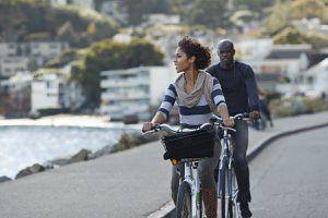 A couple ride bikes alongside the sea in a coastal city.