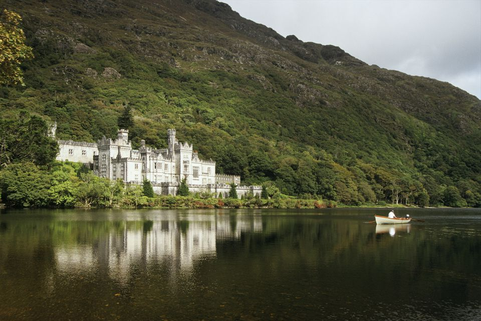 Kylemore Abbey reflected on the lake in Connemara Ireland while a boat floats by