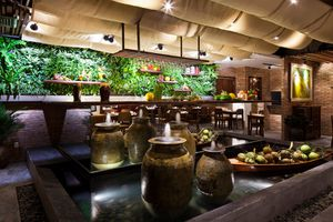 indoor decorative fountain in a restaurant with a wall of plants and a cloth ceiling