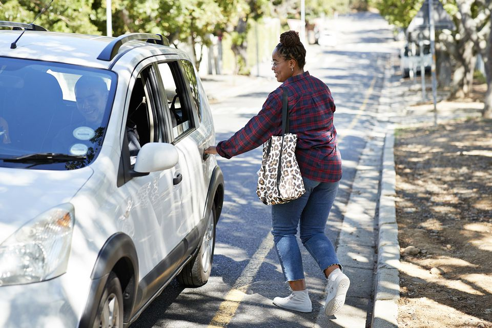 Female student opening car door on roadside