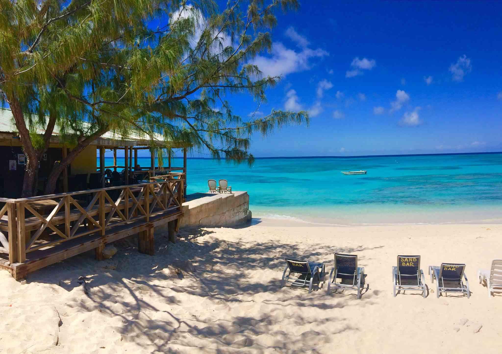 white sand beach with a restaurant and beach chairs