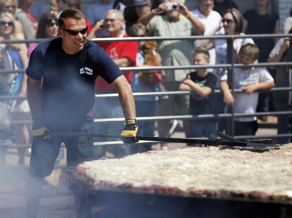 Man grilling giant hamburger patty