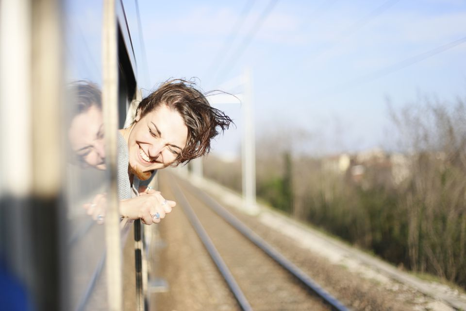 Woman on train with head out of window