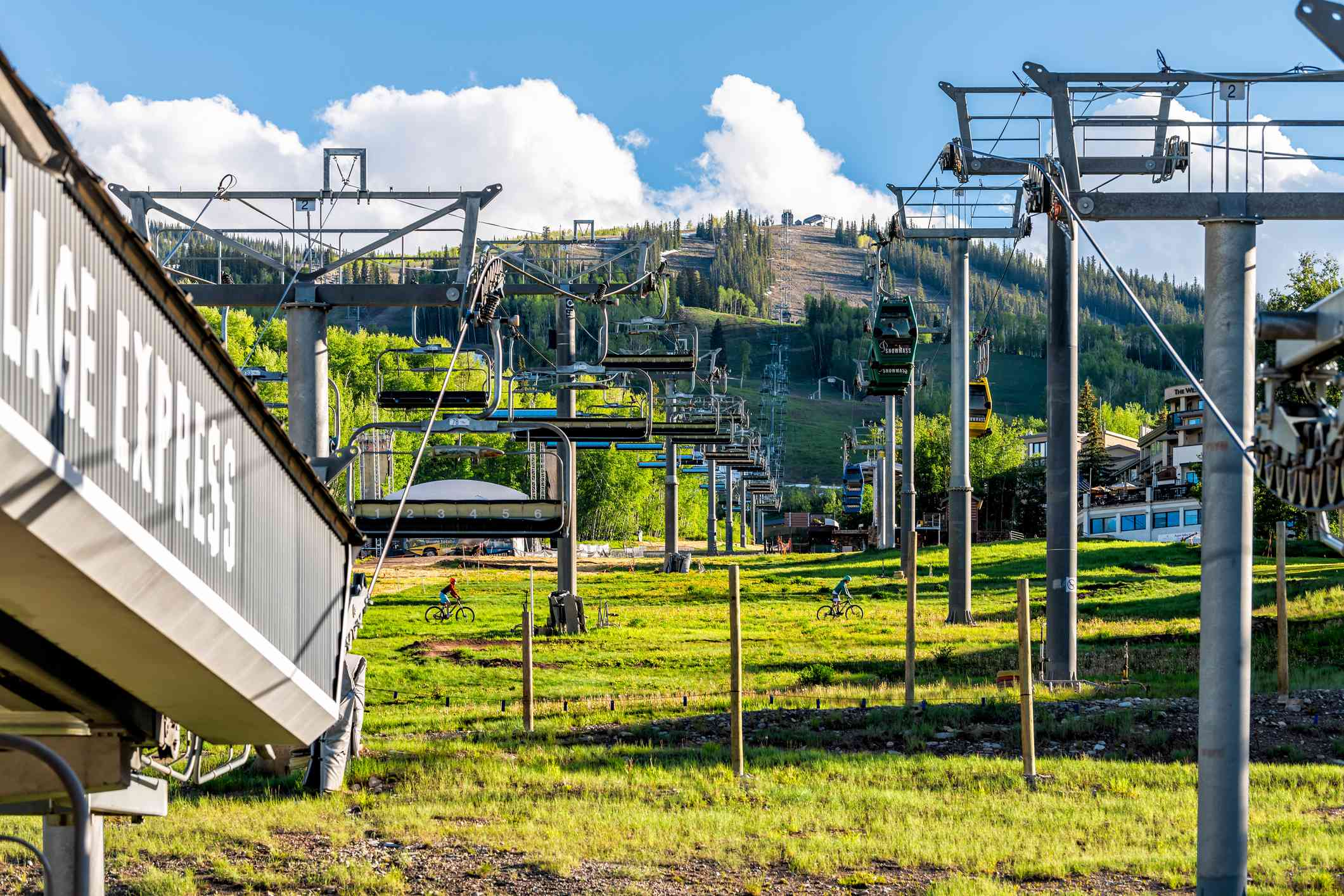 two ski lifts on a green mountain in summer