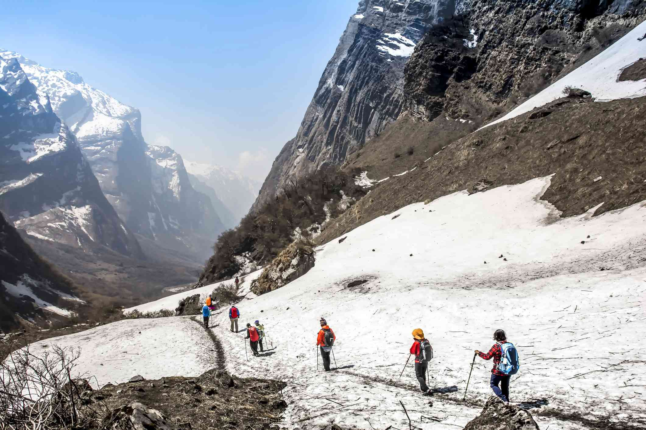 trekkers with poles walking through snow to a deep valley with snow-capped mountains